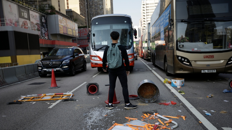 A protester stands in front of traffic stopped by debris scattered across a road in Hong Kong Monday, Nov. 11, 2019. (AP Photo/Dita Alangkara)