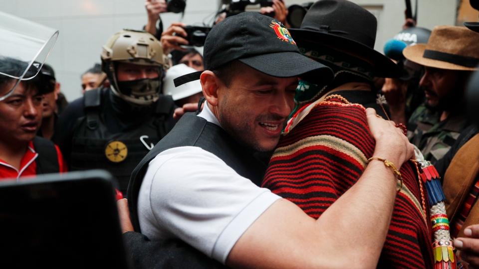 Opposition leader Luis Fernando Camacho embraces an indigenous leader outside the presidential palace in La Paz, Bolivia, after President Evo Morales announced his resignation to the presidency on Sunday, Nov. 10, 2019. (AP Photo/Juan Karita)