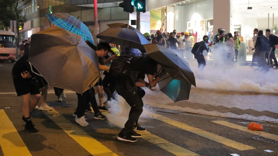 Protesters use umbrellas to protect themselves as they face police teargas in Hong Kong, Sunday, Nov. 10, 2019. (AP Photo/Kin Cheung)