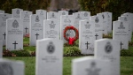 A wreath stands in front of a tombstone at the National Military Cemetery at Beechwood Cemetery in Ottawa on the day before Remembrance Day, Sunday, Nov. 10, 2019. THE CANADIAN PRESS/Justin Tang