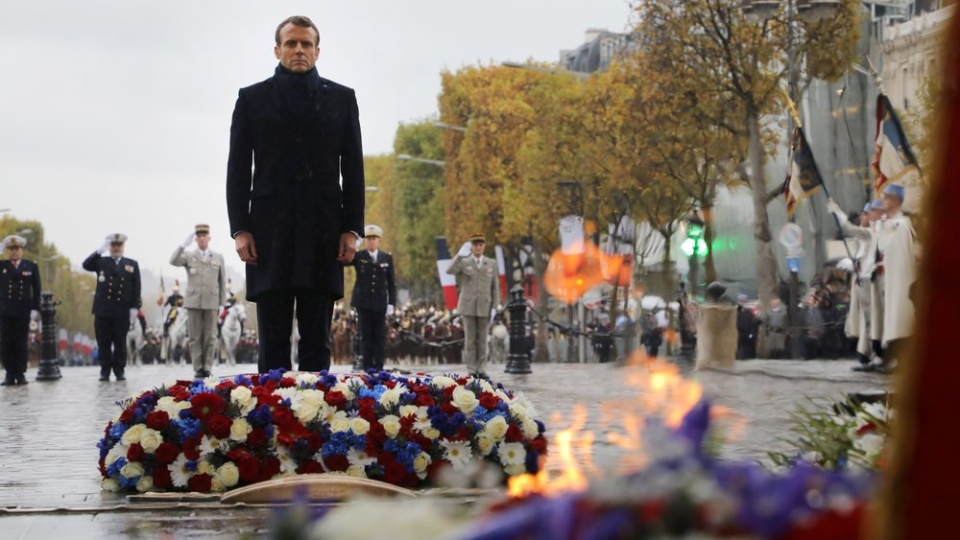 French President Emmanuel Macron stand at the tomb of the unknown soldier under the Arc de Triomphe during commemorations marking the 101st anniversary of the 1918 armistice, ending World War I, in Paris Monday Nov. 11, 2019 . (Ludovic Marin/Pool via AP)