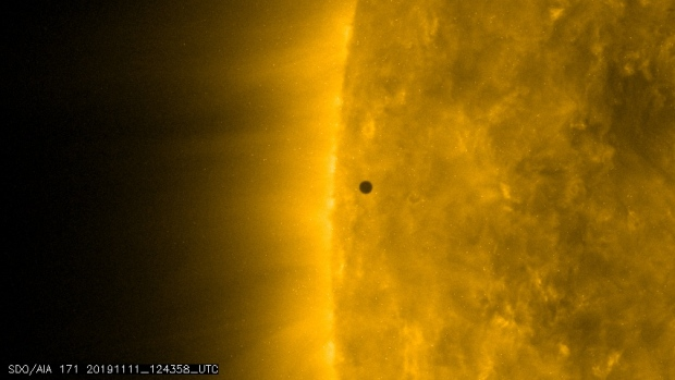 Planet Mercury passes across the face of the Sun