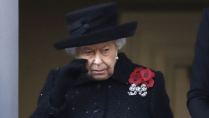 Queen Elizabeth II wipes her cheek as she watches the Remembrance Sunday ceremony at the Cenotaph in Whitehall in London, on, Nov. 10, 2019. (Matt Dunham / AP)