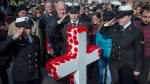 Members of the Royal Canadian Navy salute after pinning their poppies to a white cross at Remembrance Day ceremonies at the Grand Parade in Halifax on Monday, Nov. 11, 2019. THE CANADIAN PRESS/Andrew Vaughan