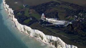 A World War II Spitfire, flies over the White Cliffs of Dover in Kent, England in a tribute to the fallen on Remembrance Day, Sunday Nov. 10, 2019. (Gareth Fuller/PA via AP)