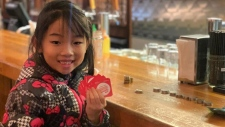 Seven-year-old Keanna Lai spent Monday afternoon handing out meal tokens she bought with money from her summertime lemonade stand. (Facebook/Ash MacLeod)