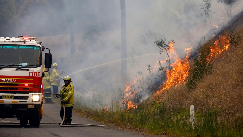 In Monday, Nov. 11, 2019, photo, firefighters work on a controlled burn in Koorainghat, New South Wales state, Australia. (Darren Pateman/AAP Images via AP)
