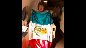 This photo released by by Mexico's Foreign Minister Marcelo Ebrard shows Bolivia's former President Evo Morales holding a Mexican flag aboard a Mexican Air Force aircraft, Monday, Nov. 11, 2019. (Mexico's Foreign Minister via AP)