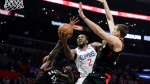 Los Angeles Clippers forward Kawhi Leonard shoots between Toronto Raptors forward Pascal Siakam, left, and Toronto Raptors center Marc Gasol during the second half of an NBA basketball game in Los Angeles, Monday, Nov. 11, 2019. (AP Photo/Chris Carlson)