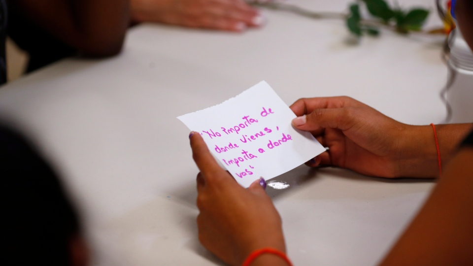 "In this Sept. 24, 2019, photo, a migrant girl in U.S. government custody holds a card that says, in Spanish, ""It doesn't matter where you come from, it matters where you are going,"" during a lesson on reproductive health and self esteem in Lake Worth, Fla. (AP Photo/Wilfredo Lee)"