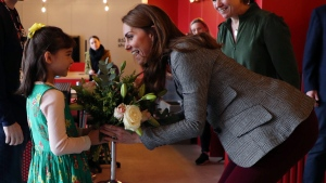 Kate, Duchess of Cambridge is presented with flowers from Michaela Conway, during a volunteer celebration event with the charity Shout at the Troubadour White City Theatre in London, Tuesday Nov. 12, 2019. (Yui Mok/Pool via AP)