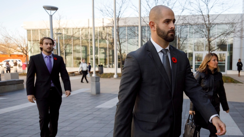 Michael Theriault, centre, and Christian Theriault, left, arrive at the Durham Region Courthouse in Oshawa, Ont., ahead of Dafonte MIller's testimony, on Wednesday, Nov. 6, 2019. (The Canadian Press)