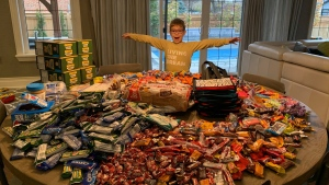 Noah Mercier, 7, poses with the donations they received after his bag of donated Halloween candy was stolen. (Tami Zuckerman-Mercier / Facebook)