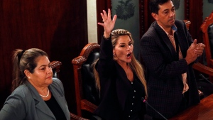 lanked by fellow lawmakers, the Senate's second vice president and opposition politician Jeanine Anez, center, declares herself the country's interim president during a session at Congress, in La Paz, Bolivia, Tuesday, Nov. 12, 2019. Anez took the step after protests and pressure from the army made former President Evo Morales quit his office. (AP Photo/Juan Karita)