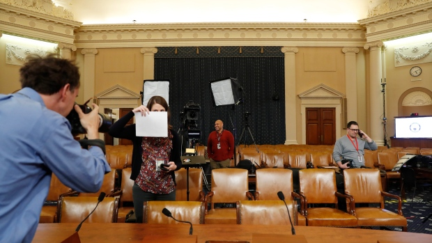 A photographer sets a white balance in the hearing room where the House will begin public impeachment inquiry hearings Wednesday, on Capitol Hill in Washington on Tuesday, Nov. 12, 2019. (AP Photo/Jacquelyn Martin)