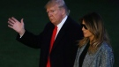 President Donald Trump and first lady Melania Trump walk on the South Lawn of the White House in Washington, Tuesday, Nov. 12, 2019, as they return from New York. (AP Photo/Steve Helber)
