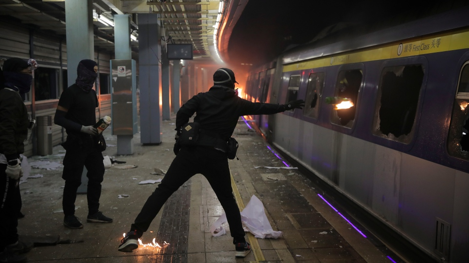 A student hurls a molotov cocktail into a train parked inside the Chinese University MTR station in Hong Kong, Wednesday, Nov. 13, 2019. (AP Photo/Kin Cheung)