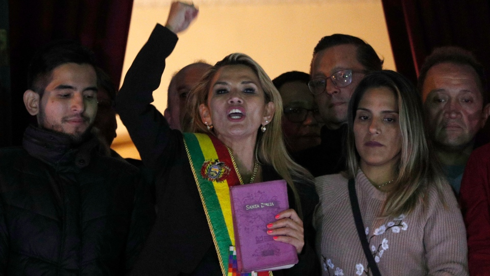 The Senate's second vice president and opposition politician Jeanine Anez, center, wearing the Presidential sash addresses the crowd from the balcony of the Quemado palace after she declared herself interim president of the country, in La Paz, Bolivia, Tuesday, Nov. 12, 2019. (AP Photo/Juan Karita)