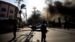 Police stands guard after a factory hit by a rocket caught fire in Sderot, southern Israel , Israel, Tuesday, Nov. 12 2019. (AP Photo/Tsafrir Abayov)
