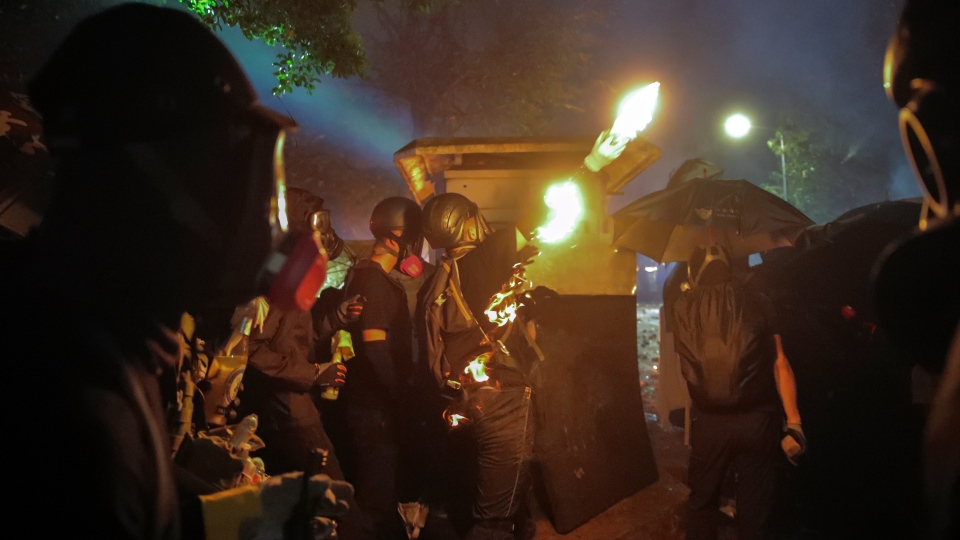 A student prepares to hurl a molotov cocktail toward police during clashes at the Chinese University in Hong Kong, Tuesday, Nov. 12, 2019. (AP Photo/Kin Cheung)