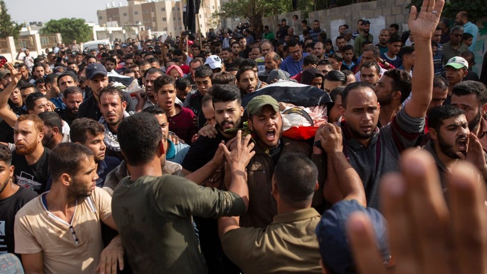 Mourners chant angry slogans as they carry the body of Islamic Jihad militant, Abdullah Al-Belbesi, 26, who was killed in Israeli airstrikes, during his funeral, in the town of Beit Lahiya, Northern Gaza Strip, Wednesday, Nov. 13, 2019. (AP Photo/Khalil Hamra)