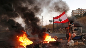 An anti-government protester carries her national flag past burning tires blocking the main highway during protests against the corruption in Khaldeh, south of Beirut, Lebanon, Wednesday, Nov. 13, 2019. (AP Photo/Hussein Malla)