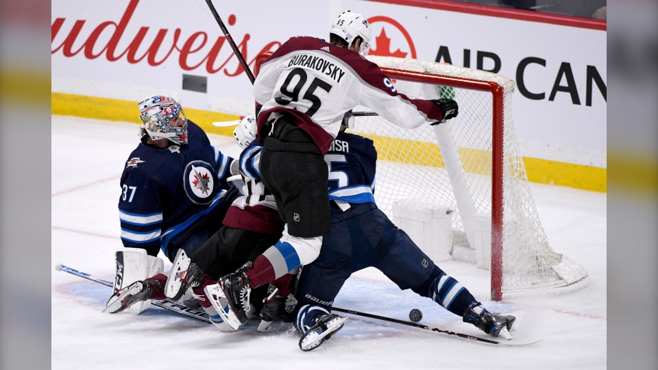 Colorado Avalanche's Andre Burakovsky (95) looks for the rebound after a save by Winnipeg Jets goaltender Connor Hellebuyck (37) during third period NHL action in Winnipeg on Tuesday, Nov. 12, 2019. (Source: The Canadian Press/Fred Greenslade)