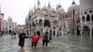 People wade through water in a flooded St. Mark's Square in Venice, Italy, Wednesday, Nov. 13, 2019. The high-water mark hit 187 centimeters (74 inches) late Tuesday, Nov. 12, 2019, meaning more than 85% of the city was flooded. The highest level ever recorded was 194 centimeters (76 inches) during infamous flooding in 1966. (AP Photo/Luca Bruno)