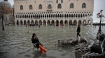 A woman sits in a chair in a flooded St. Mark's Square, in Venice, Wednesday, Nov. 13, 2019. (AP Photo/Luca Bruno)