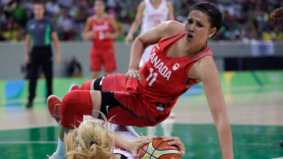 Canada forward Natalie Achonwa (11) falls as Spain forward Laura Gil controls the ball during the second half of a women's basketball game at the Youth Center at the 2016 Summer Olympics in Rio de Janeiro, Brazil, Sunday, Aug. 14, 2016. (AP Photo/Carlos Osorio)