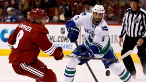 Vancouver Canucks' Jason Garrison (5) passes the puck in front of Phoenix Coyotes' Matthew Lombardi, left, during the first period in an NHL hockey game on Thursday, March 21, 2013, in Glendale, Ariz. THE CANADIAN PRESS/AP, Ross D. Franklin