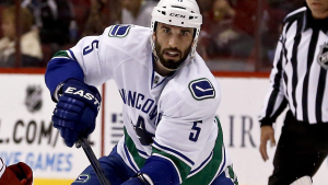 Vancouver Canucks' Jason Garrison (5) passes the puck in front of Phoenix Coyotes' Matthew Lombardi, left, during the first period in an NHL hockey game on Thursday, March 21, 2013, in Glendale, Ariz. (AP / Ross D. Franklin)