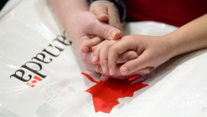 A mother holds the hands of her daughter as they become new Canadians and take the Oath of Citizenship on Parliament Hill in Ottawa on April 17, 2019. (THE CANADIAN PRESS / Sean Kilpatrick)