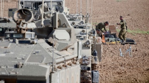 Israeli soldiers prepare their armored vehicles at a gathering point near the Israel--Gaza Border, Wednesday, Nov. 13, 2019. (AP Photo/Ariel Schalit)