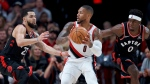 Portland Trail Blazers guard Damian Lillard, center, looks to pass the ball as Toronto Raptors guard Fred VanVleet, left, and guard Terence Davis, right, defend during the second half of an NBA basketball game in Portland, Ore., Wednesday, Nov. 13, 2019. (AP Photo/Craig Mitchelldyer)