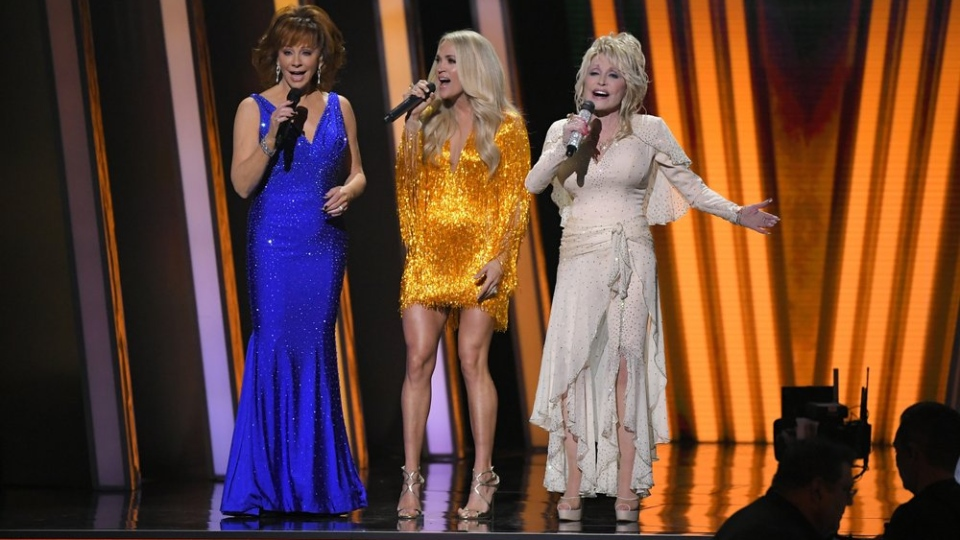 Hosts Reba McEntire, from left, Carrie Underwood and Dolly Parton appear at the 53rd annual CMA Awards at Bridgestone Arena, Wednesday, Nov. 13, 2019, in Nashville, Tenn. (AP Photo/Mark J. Terrill)