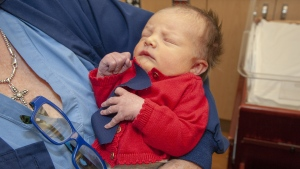A baby at the West Penn Hospital is dressed up in a red cardigan and tie to celebrate World Kindness Day and Cardigan Day in honor of Mister Rogers. (Allegheny Health Network/CNN)