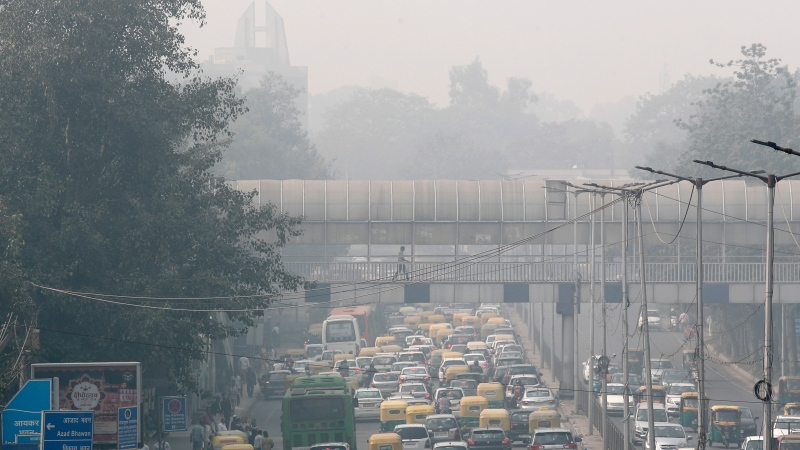 A pedestrian uses a foot over bridge to cross over as the city is enveloped under thick smog in New Delhi, India, Tuesday, Nov. 12, 2019. (AP Photo/Manish Swarup)