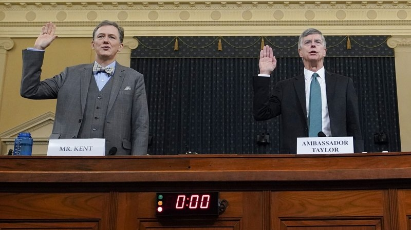 Career Foreign Service officer George Kent and top U.S. diplomat in Ukraine William Taylor, right, are sworn in to testify during the first public impeachment hearing of the House Intelligence Committee on Capitol Hill, Wednesday Nov. 13, 2019, in Washington. (Joshua Roberts/Pool via AP)