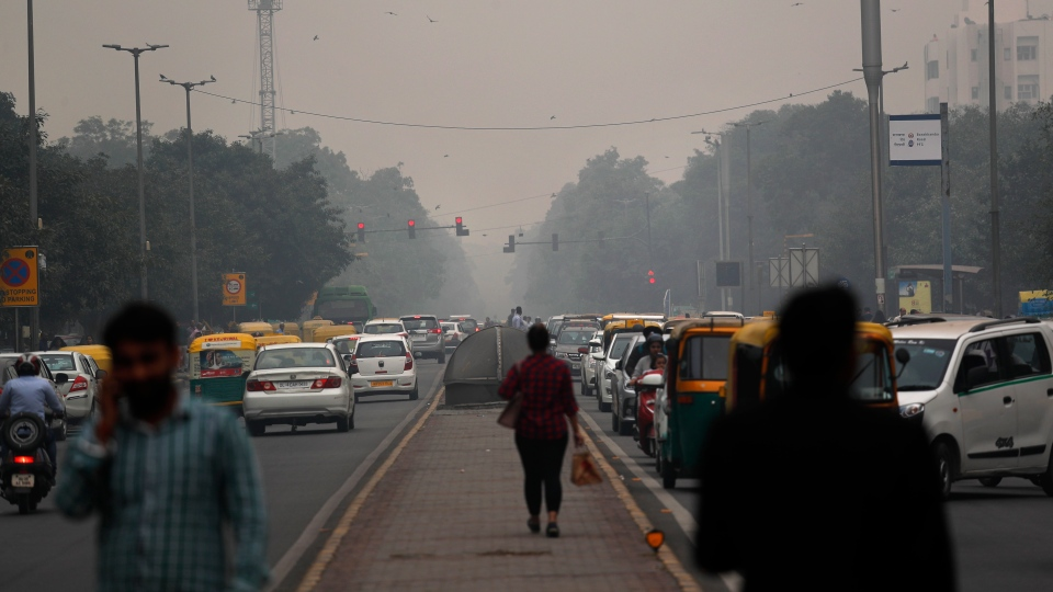 Commuters walk across amidst thick layer of smog in New Delhi, India, Thursday, Nov. 14, 2019. (AP Photo/Manish Swarup)