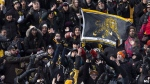 Hamilton Tiger-Cats fans try to catch a ball thrown into the stands during the first half CFL Football division semifinal game action against the B.C. Lions in Hamilton, Ont. on Sunday, Nov. 11, 2018. The Hamilton Tiger-Cats are a feel-good story for a city that has dealt with its share of bad news this year. (THE CANADIAN PRESS/Peter Power)