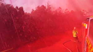 Sydney firefighters drenched in retardant airdrop