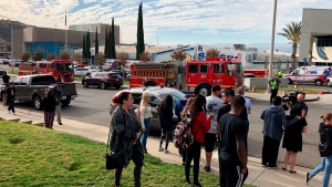 People wait for students and updates outside of Saugus High School after reports of a shooting on Thursday, Nov. 14, 2019, in Santa Clarita, Calif. (AP Photo/Marcio Jose Sanchez)