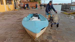 An elderly man passes by a boat left ashore following a flooding in Venice, Italy, Thursday, Nov. 14, 2019. (Andrea Merola/ANSA via AP)