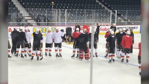 Flames staff and emergency crews attend to TJ Brodie during Flames' practice on Nov. 14 after the defenceman fell to the ice and began to convulse