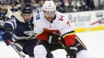 Calgary Flames' TJ Brodie, right, keeps the puck away from Columbus Blue Jackets' Markus Nutivaara, of Finland, during the first period of an NHL hockey game Tuesday, Dec. 4, 2018, in Columbus, Ohio. (AP Photo/Jay LaPrete)