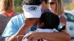 Ella Cabigting is embraced by her father Emerson as they reunite following a shooting at Saugus High School that injured several people, Thursday, Nov. 14, 2019, in Santa Clarita, Calif. (AP Photo/Ringo H.W. Chiu)