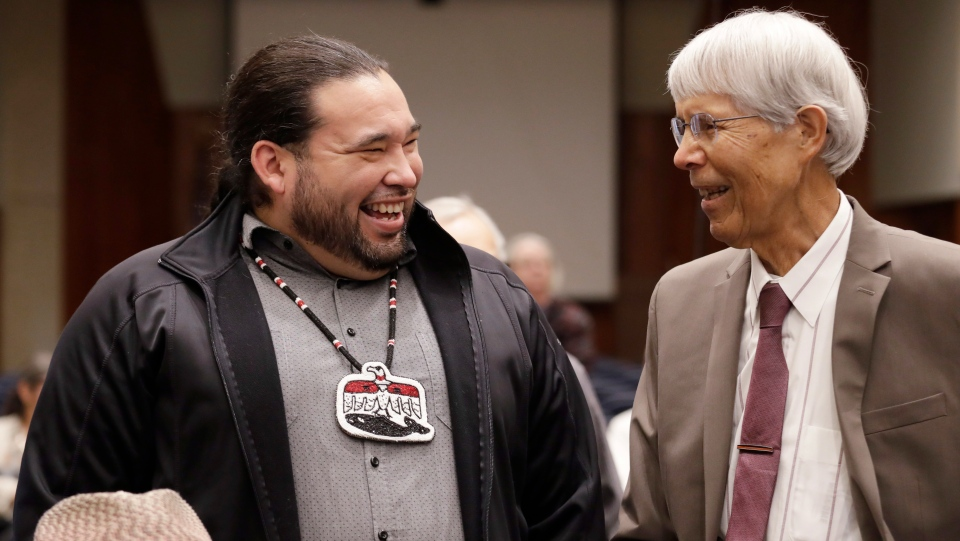 Makah Tribal Council Member Patrick DePoe, left, talks with Marine Mammal Commission Commissioner Michael F. Tillman before a federal court hearing to help determine whether DePoe's small American Indian tribe can once again hunt whales, Thursday, Nov. 14, 2019, in Seattle. The symbol DePoe wears is from the tribe's flag, and includes bird and whale symbols. (AP Photo/Elaine Thompson)