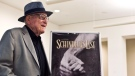 FILE - In this Wednesday, July 22, 2015 file photo, Branko Lustig stands next to a poster of the film Schindler's List at Yad Vashem Holocaust memorial in Jerusalem. (Nir Elias/Pool Photo via AP, file)