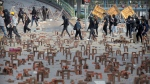In this Nov. 14, 2019, photo, protesters walk past barricades of bricks on a road near the Hong Kong Polytechnic University in Hong Kong. (AP Photo/Kin Cheung, File)